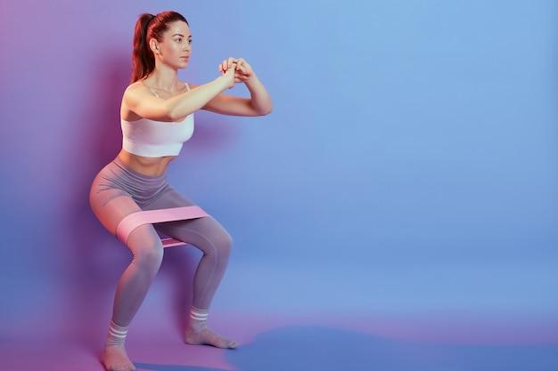 Foto van fitness meisje in stijlvolle sportkleding squats met rubberen band op muur van blauw en roze muur. sportieve atletische vrouw gehurkt, sit-ups doen.