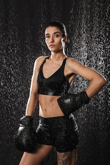 Foto van fitness vrouw met haar in paardenstaart arm zetten in bokshandschoenen op taille en kijken op camera onder waterdruppels, geïsoleerd op zwarte achtergrond