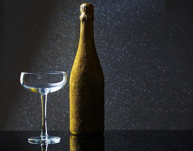 Foto van fles champagne in gouden wikkel met leeg wijnglas