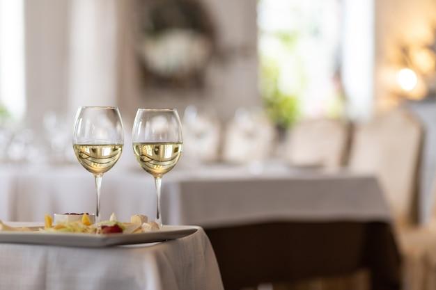 Foto van fles met champagne gieten in wijnglazen op grijze achtergrond