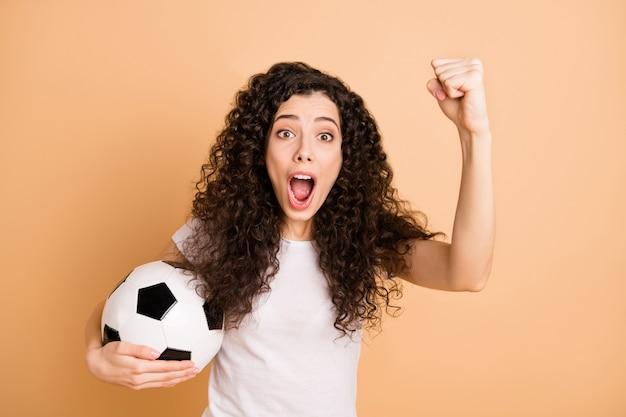 Foto van funky dame met grote witte zwarte lederen voetbalbal ter ondersteuning van favoriete team vuist dragen witte vrijetijdskleding geïsoleerde beige pastelkleur achtergrond