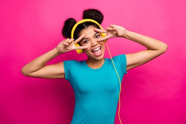 Foto van funky donkere huid dame luistert muziek met v-teken symbolen in de buurt van de ogen