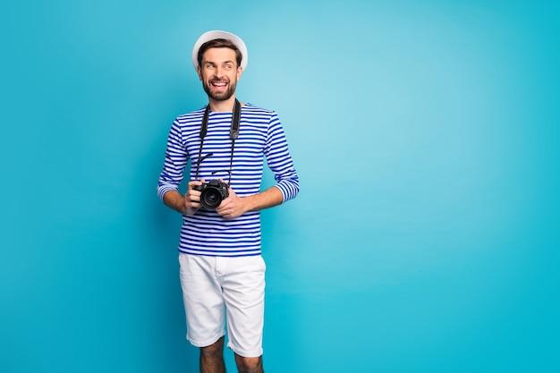 Foto van funky knappe kerel toerist houden professionele digitale lens camera reizen naar het buitenland kijken lege ruimte dragen gestreepte matroos shirt pet korte broek geïsoleerde blauwe kleur