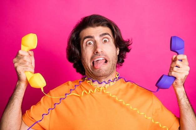 Foto van funky man met tong uit zijn armen houdt twee telefoons vast, hangen kabels dragen oranje t-shirt geïsoleerd roze kleur achtergrond