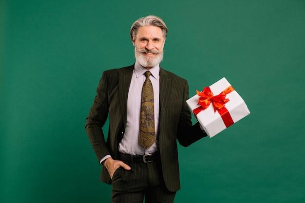 Foto van funky volwassen man amour in kaki pak cupido karakter rol met grote geschenkdoos op een valentijnsdag geïsoleerde groene kleur achtergrond