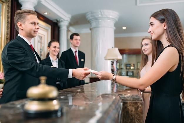 Foto van gasten die sleutelkaart krijgen in hotel,