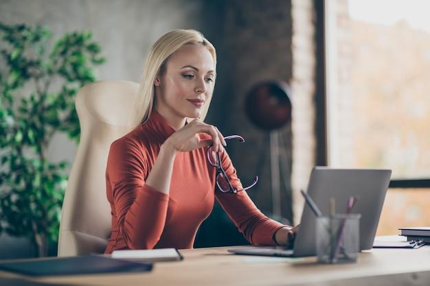 Foto van geconcentreerde gefocuste vrouw die het analyseren van de mogelijkheden van financiële groei van het bedrijf in dit jaar vergelijkt