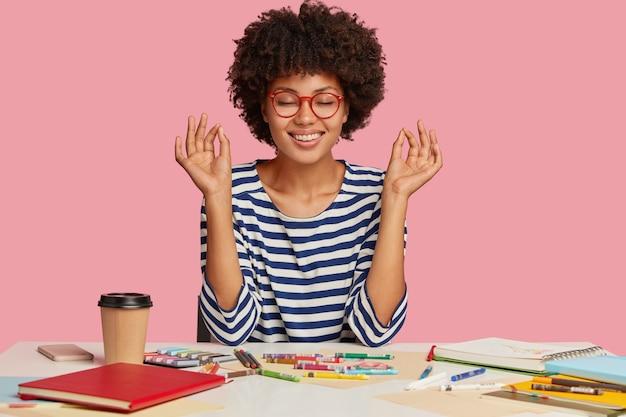 Foto van geconcentreerde ontspannen donkere jonge vrouw maakt goed gebaar met beide handen, mediteert op de werkplek, voelt zich kalm en ontspannen, gekleed in gestreepte kleding, geïsoleerd op roze, tekent foto