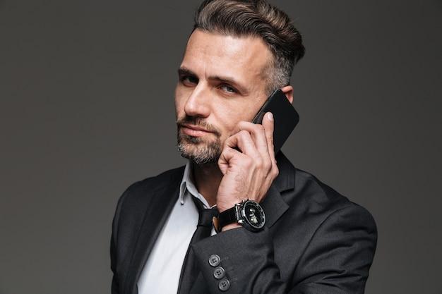 Foto van geconcentreerde rijpe kerel die in zwart kostuum op camera kijkt terwijl het hebben van mobiel gesprek, dat over donkergrijs wordt geïsoleerd