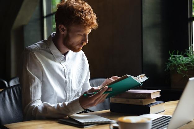 Foto van geconcentreerde roodharige bebaarde student, voorbereiding voor universitair examen in een café