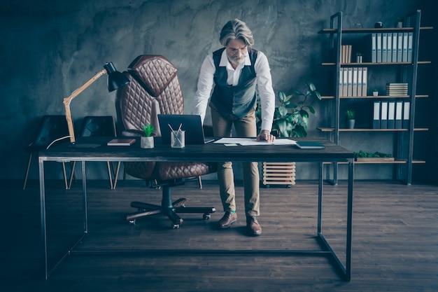 Foto van geconcentreerde senior manager gelezen document op bureau in kantoor
