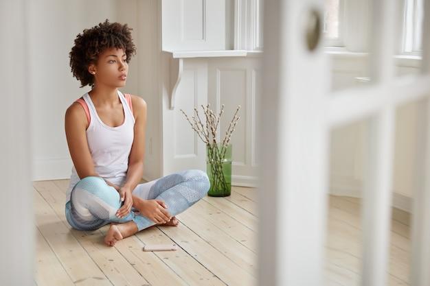Foto van geconcentreerde zwarte vrouw zit gekruiste benen op houten vloer