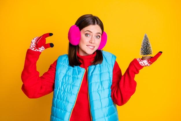 Foto van gefrustreerd meisje voelt zich schuldig dat ze kiest voor kleine, groenblijvende kerstboom bijt lippen tanden draagt stijlvolle trendy trui geïsoleerd over heldere glans kleur achtergrond