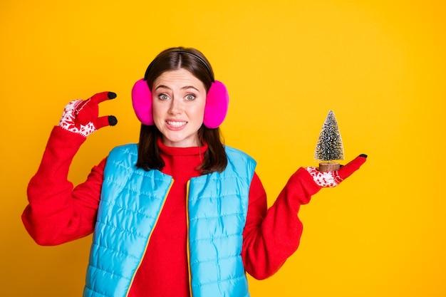 Foto van gefrustreerd meisje voelt zich schuldig over het kiezen van een kleine groenblijvende kerstboom, draag een roze trui geïsoleerd over een glanzende kleurachtergrond