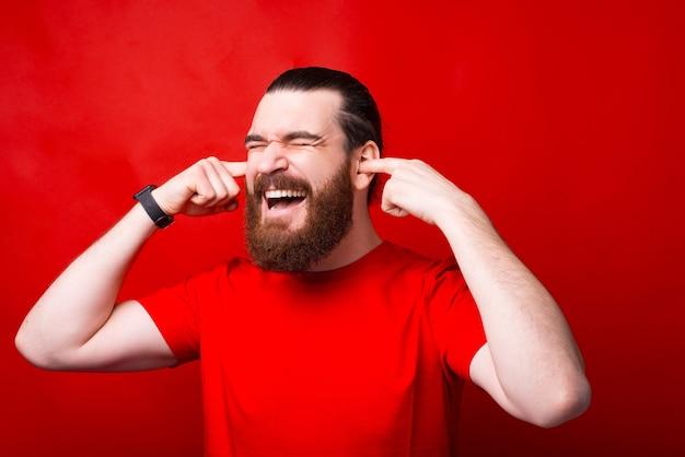 Foto van gefrustreerde bebaarde man sluitende oren met vingers over rode muur