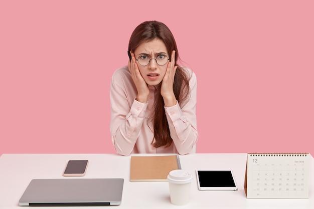 Foto van gefrustreerde blanke vrouw gekleed in een elegant shirt, poseert alleen op de werkplek, heeft dingen netjes gerangschikt, draagt een ronde bril