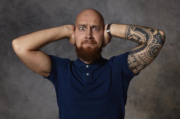 Foto van gefrustreerde emotionele europese man met geschoren hoofd en pluizige baard stijlvol haar grimassen, gaan huilen vanwege hard geluid of ruzie met zijn vriendin, zijn oren bedekkend met handen