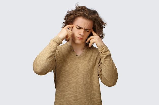 Foto van gefrustreerde, gestreste, zieke jonge blanke die zich depressief voelt vanwege vreselijke hoofdpijn, fronsen, de ogen gesloten houden en de vingers op zijn slapen drukt, in een poging pijn te verzachten