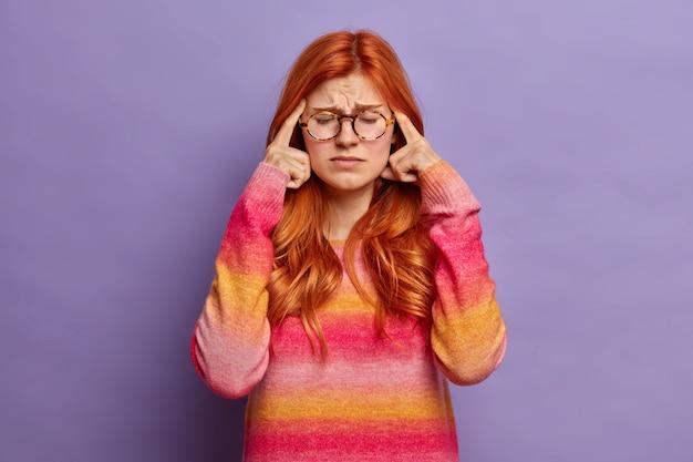 Foto van gefrustreerde roodharige jonge vrouw houdt vingers op slapen lijdt aan hoofdpijn of ernstige migraine sluit ogen om pijn te onthullen draagt bril en trui.