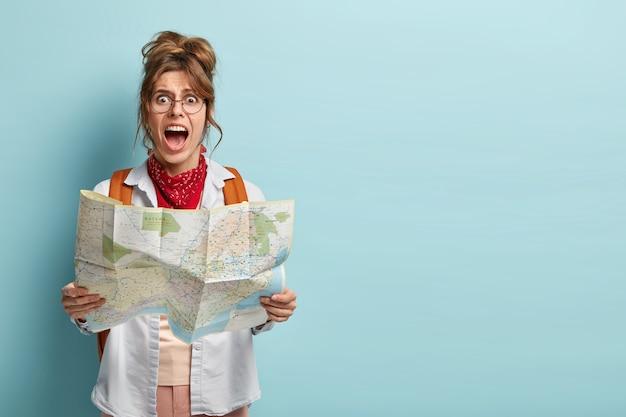 Foto van gefrustreerde vrouwelijke reiziger verdwaald in de stad, kijkt depressief naar de papieren kaart en roept van wanhoop
