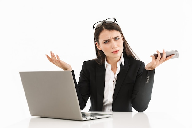 Foto van gefrustreerde vrouwelijke werkneemster, gekleed in formele kleding, zittend aan een bureau en werkend op een laptop op kantoor geïsoleerd over een witte muur