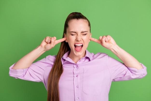 Foto van gefrustreerde woede meisje kan niet luisteren naar luide muziek lawaai sluit dekking wijsvinger schreeuw draag lila shirt geïsoleerd over groene kleur achtergrond