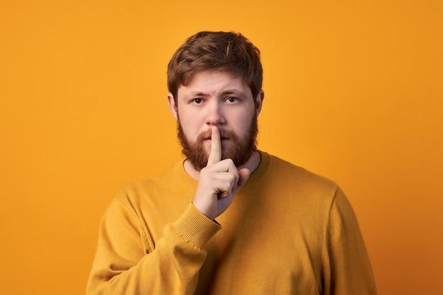 Foto van geheime gember stijlvolle mannelijke man stilte teken vertoont, heeft verbaasde uitdrukking, schrik van onthullend geheim, nonchalant gekleed, poseert alleen tegen witte achtergrond