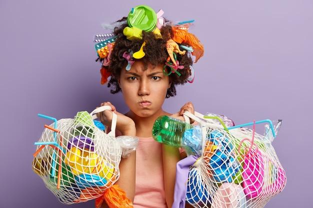 Foto van geïrriteerd vrouwelijk model heeft een boze uitdrukking, geeft om de netheid van onze planeet, draagt plastic afval, haalt afval op tijdens de dag van de aarde, vecht tegen besmetting of vervuiling