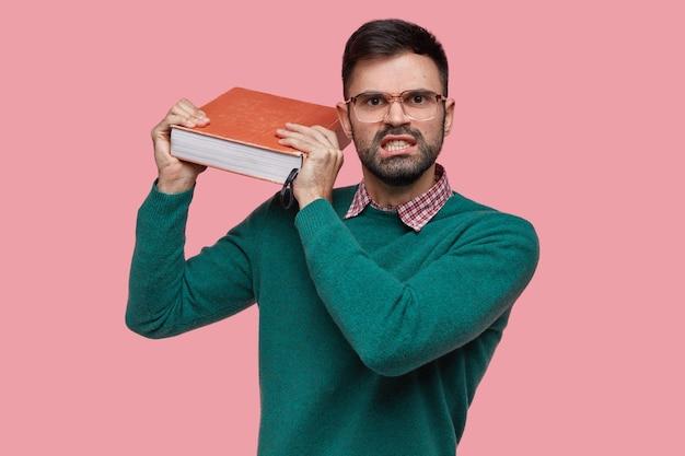 Foto van geïrriteerde europese ongeschoren man houdt dikke rode oude encyclopedie vast, voelt zich geïrriteerd door het leren van nieuw materiaal