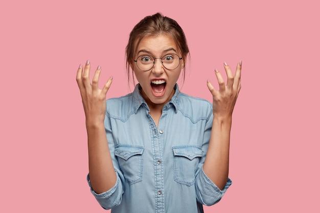 Foto van geïrriteerde jonge vrouwengebaren boos