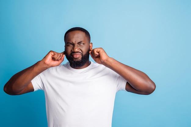Foto van geïrriteerde man vingers dicht oren kijken kant lege ruimte draag wit t-shirt over blauwe achtergrond