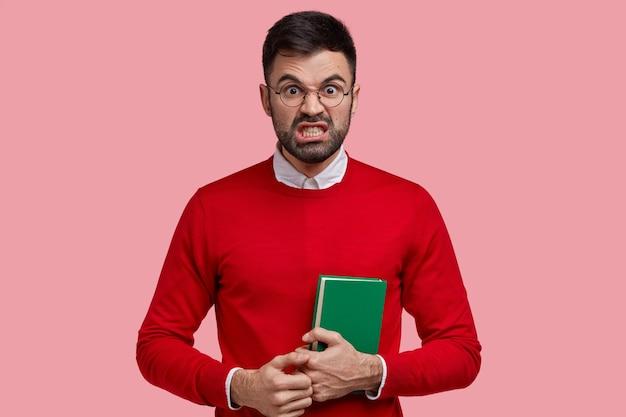 Foto van geïrriteerde, pissige student kijkt in ongenoegen en woede, klemt zijn tanden, staart, draagt een ronde bril