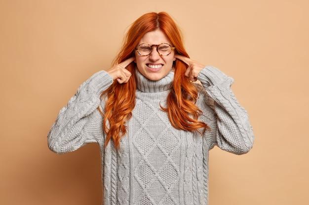 Foto van geïrriteerde roodharige jonge vrouw klemt tanden en stekkers oren grijnst gezicht gekleed in casual winter grijze trui negeert het luisteren irritant geluid of lawaai.