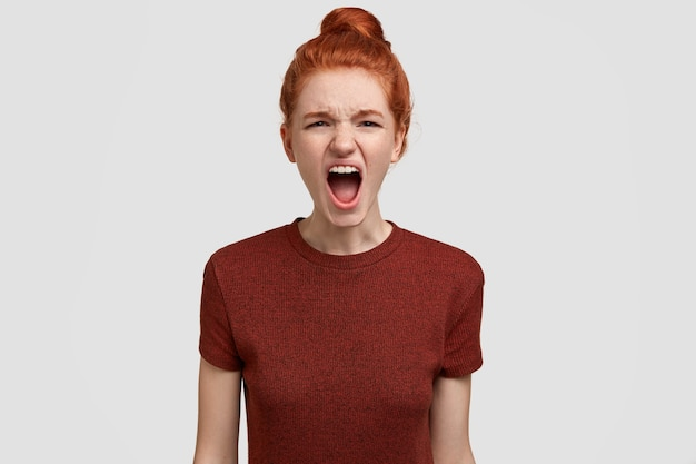 Foto van geïrriteerde roodharige vrouwelijke tiener schreeuwt luid, voelt zich geïrriteerd