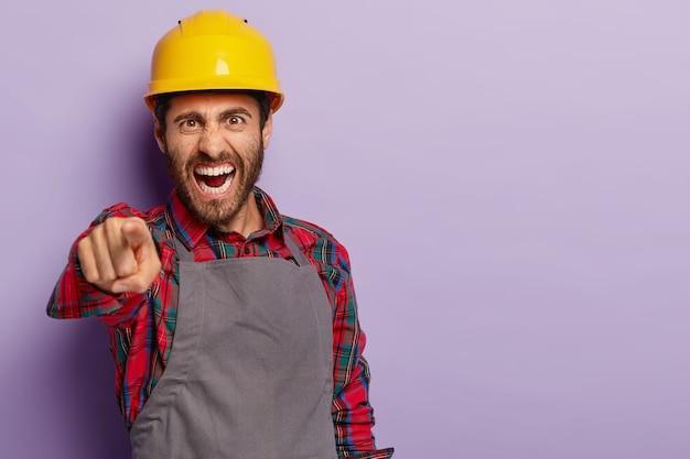 Foto van geïrriteerde voorman wijst, schreeuwt van verwijt, schreeuwt boos naar collega, draagt gele helm, shirt en schort. geïrriteerde bouwer lost probleem op het werk op