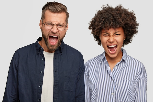 Foto van gekke boze jonge man en vrouw van verschillende rassen roepen geïrriteerd uit