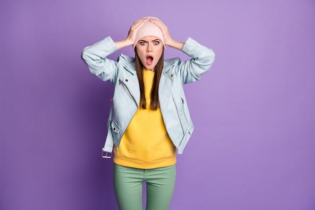 Foto van gekke geschokte aantrekkelijke dame tiener houdt armen op hoofd open mond luister vreselijk quarantaine nieuws draag casual hoed blauwe moderne jas broek geïsoleerde paarse kleur achtergrond