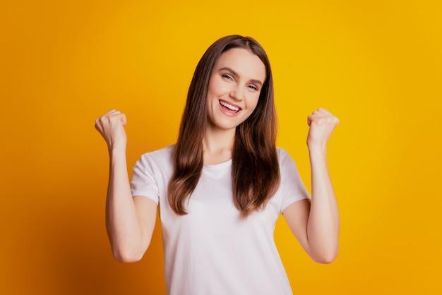 Foto van gekke grappige dame die vuisten opheft winnaar concept draagt een wit t-shirt poseren op gele achtergrond