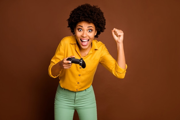 Foto van gekke grappige donkere huid krullende dame houdt joystick varen videogame verslaafd gamer online teamleider dragen geel shirt groene broek geïsoleerde bruine kleur
