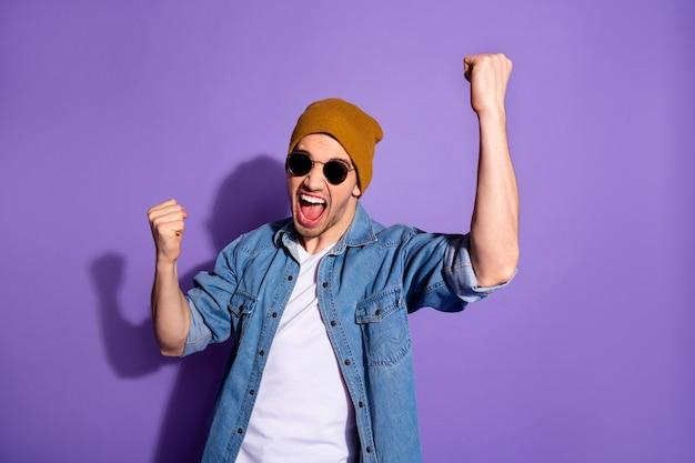 Foto van gekke opgewonden extatische dolgelukkige kerel die zijn handen opheft in euforie van zegevierende glorie terwijl hij geïsoleerd op paarse levendige kleurenachtergrond