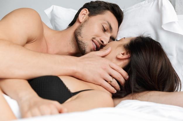Foto van geliefde paar man en vrouw samen knuffelen, liggend in bed thuis of hotel appartement