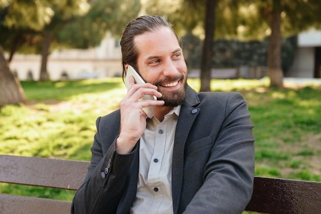 Foto van gelukkig bebaarde man 30s in formeel pak met mobiele gesprek, zittend op een bankje in het stadspark tijdens zonnige dag