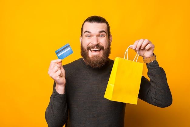 Foto van gelukkig bebaarde man met creditcard en gele boodschappentas, online aankoop