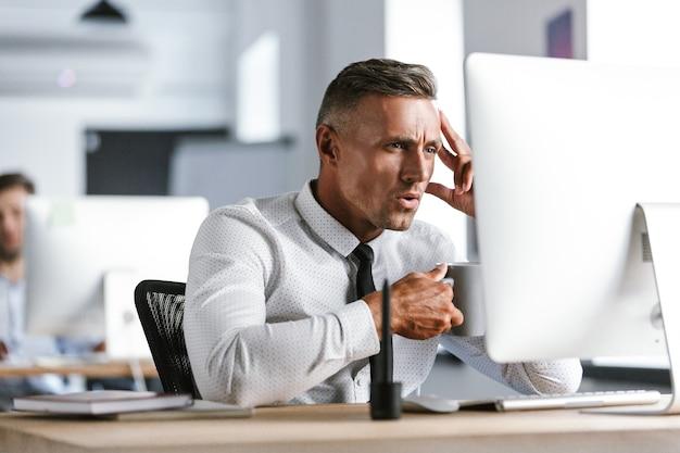 Foto van gelukkig directeur man 30s dragen wit overhemd en stropdas thee drinken uit de beker, zittend door de computer op kantoor