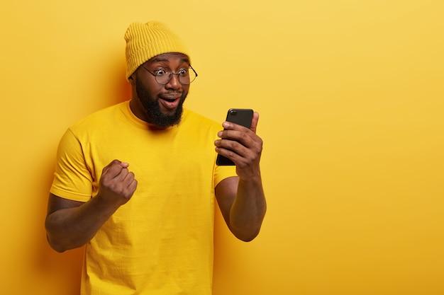 Foto van gelukkig donkere man viert overwinning van favoriete team, resultaten van spel op internet leest, kijkt dolblij op smartphone-display