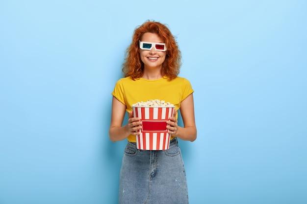 Foto van gelukkig gember charmant meisje houdt emmer met popcorn