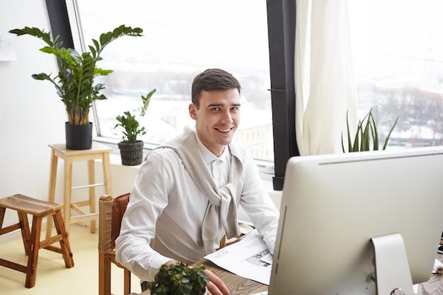 Foto van gelukkig lachend jonge getalenteerde mannelijke architect bouwproject ontwerpen in moderne kantoren, plan tekenen en bestuderen van blauwdrukken op bureau, genieten van creatieve proces. baan en beroep