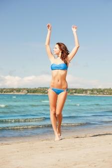 Foto van gelukkig lachende vrouw wandelen op het strand.