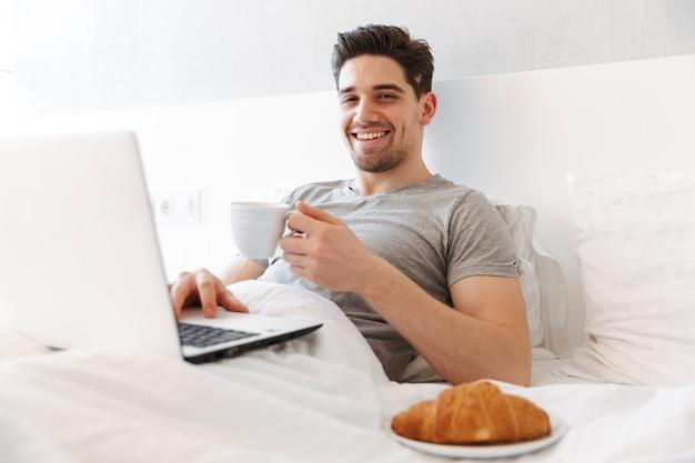 Foto van gelukkig man in casual kleding ontbijten, liggend in bed met laptop en kopje koffie
