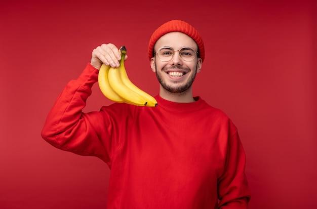 Foto van gelukkig man met baard in glazen en rode kleding. houdt bananen en glimlacht, gezonde levensstijl, geïsoleerd op rode achtergrond.